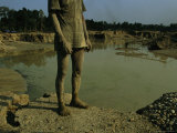 Gold Miner Standing Next To Runoff Pond Laced with Mercury and Cyanide Photographic Print by Steve Winter