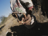 Close View of a San Bushman Holding a Slingshot Photographic Print by Joy Tessman