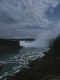 Distant View of Mist-Shrouded Niagara Falls Under a Cloudy Sky Photographic Print by Todd Gipstein
