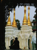 Silhouetted Monk Meditating Near Temple with Gilded Spires Photographic Print by Steve Winter