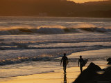 Surfers are Silhouetted by the Sunset on a Beach in Santa Barbara Photographic Print by Rich Reid