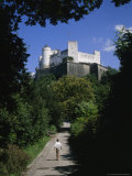 Salzburg Castle Dwarfs a Man Walking Towards It Photographic Print by Taylor S. Kennedy