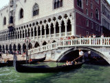 Gondolier Maneuvers His Boat Under a Bridge Crossing a Canal Photographic Print by Rex Stucky