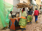 Women Carrying Firewood Past Tailor in Lane of Old City of Harar Photographic Print by Andrew Burke