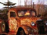 Rusty Old Truck Strung with Christmas Lights, with Santa Claus at Wheel Photographic Print by Judy Bellah