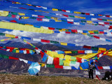 Pilgrim Stringing Up Prayer Flags with Mountains in Background Photographic Print by Krzysztof Dydynski