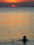 Sun Setting over Sea with Silhouette of Person Swimming Photographic Print by John Borthwick