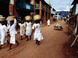 Women of a Religious Community Carry Baskets on their Heads Through the Soatanana Village Photographic Print by Olivier Cirendini