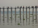 People Ride their Bicycles Along U Bein's Bridge That Runs Down the Taungthaman Lake Photographic Print by David Greedy