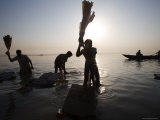 Morning Silhouettes of People as They Thrash the Dirt Out of their Clothes, Ganges River Photographie par Orien Harvey