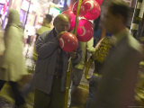 Man Blowing Up Balloons Outside a Mosque Photographic Print by Gavin Quirke