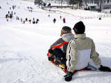 Two People on Sled at Top of Run with People Below Photographic Print by Brian Cruickshank