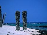 Two Tall Wooden Ki'I Stand Guard Near Hale O Kaewe Heiau at Pu`Uhonua O Honaunau Photographic Print by Ann Cecil