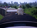 Man Sitting Alone on the Roof of a Carriage of the Battambang to Phnom Penh Train Photographic Print by Andrew Burke