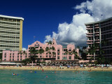 Exterior of the Royal Hawaiian Hotel with Waikiki Beach in Foreground Photographic Print by Ann Cecil