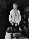 A Little Boy Receiving a Pair of New Boots and Clothing from Swiss Relief Workers Premium Photographic Print by Tony Linck