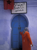 Woman Exits thru Moorish-Style Blue Door, Morocco Photographic Print by John & Lisa Merrill