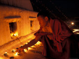 Monk Lighting Butter Lamps at Boudnath, Kathmandu, Nepal Photographic Print by Vassi Koutsaftis