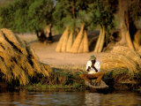 Local Man Fishing and Piles of Straw for Hatch, Okavango Delta, Botswana Photographic Print by Pete Oxford