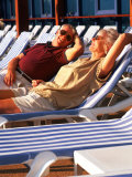 Retired Couple Lounging in Deck Chairs on a Cruise Ship Photographie par Bill Bachmann