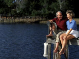 Healthy Couple Sitting on the Dock by a Lake Photographic Print by Bill Bachmann