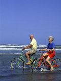 Retired Couple Riding Bikes at the Beach Photographic Print by Bill Bachmann