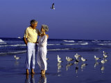 Retired Couple Relaxing on the Beach Photographic Print by Bill Bachmann