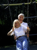 Healthy Couple in Park on Swing Photographic Print by Bill Bachmann