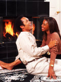 African-American Couple Sitting by the Fireplace Photographic Print by Bill Bachmann