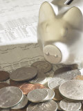 Silver Piggy Bank on Top of Pile of American Coins and Stock Market Report Photographic Print