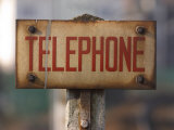 Close-Up of Singed Telephone Sign Outdoors Photographic Print
