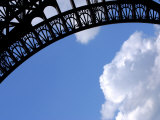 Intricate Architectural Designs on Eiffel Tower Against a Blue Sky with Fluffy Clouds Photographic Print