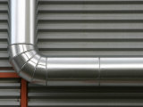 Close-Up of Industrial Pipe Against Metal Wall Photographic Print