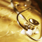Stethoscope Lying over Gold Coins Photographic Print