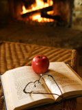 Relaxing Scene of an Apple and Eyeglasses on Open Book by Fireplace at Home Photographic Print