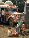 Man Seated with Two Young Boys in Front of a Wildly Painted School Bus, Woodstock Music Art Fest Lmina fotogrfica de primera calidad por John Dominis