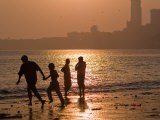 Silhouetted Figures on Chowpatty Beach, Mumbai, Maharashtra State, India Photographic Print by Abraham Nowitz