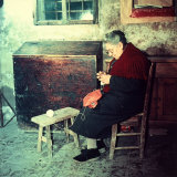 Elderly Woman Sitting and Working on a Shirt in a Rural House Photographic Print by A. Villani