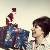 Smiling Woman Looking at a Christmas Present Held in Front of Her Photographic Print by A. Villani
