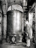 Elderly Worker Waits for Liquid Contained in a Distillation Apparatus Photographic Print by A. Villani