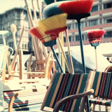 Some Brooms of Various Colors Leaning on Some Chairs Made of Wood and Colored Stripes Photographic Print by A. Villani