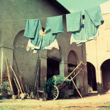 Green Pants Hanging on a Washing Line, in a Barn Yard Photographic Print by A. Villani