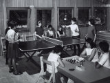 Two Girls Sitting at a Table are Playing Draughts, Four Young Woman are Playing Ping-Pong Photographic Print by A. Villani