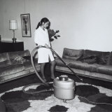 Young Woman Using a Vacuum Cleaner on a Carpet in a Lounge Photographic Print by A. Villani