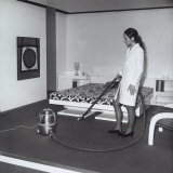 Young Woman Using a Vacuum Cleaner on the Carpet in a Bedroom Photographic Print by A. Villani
