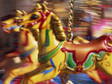 Motion Blur of Brightly Painted Merry Go Round Horses at Speed, Skegness, Lincolnshire, England Photographic Print by Neale Clarke