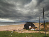 Stormy Sky with Fisherman's Hut and Net Drying Poles, Redpoint Beach, Wester Ross, Scotland, UK Photographic Print by Neale Clarke
