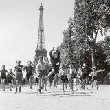 Rennende kinderen in park bij Eiffeltoren, Parc du Champs de Mars Poster van Robert Doisneau