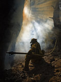 A firefighter blasts water in attempts to drown stubborn flames Photographic Print by Mark Thiessen