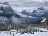 Rising fog and snow-dusted evergreens and mountains at Logan Pass Photographic Print by Michael Melford